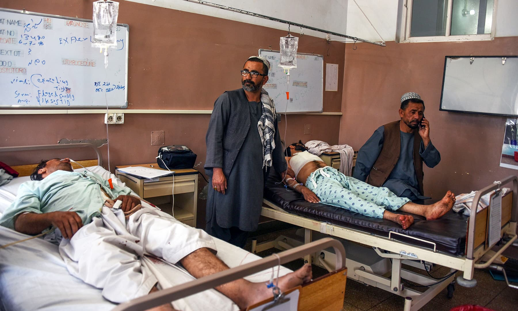 Wounded men receive treatment at a hospital following a blast in Kandahar Province. — AFP