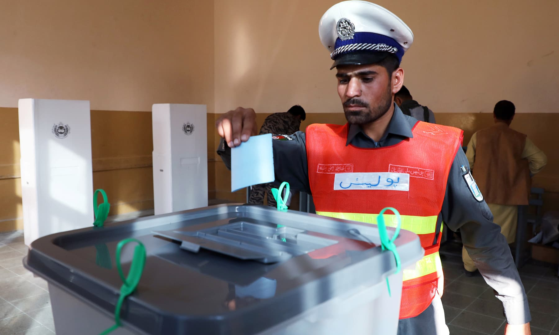 An Afghan policeman casts his vote at a polling station in Kabul. — Reuters