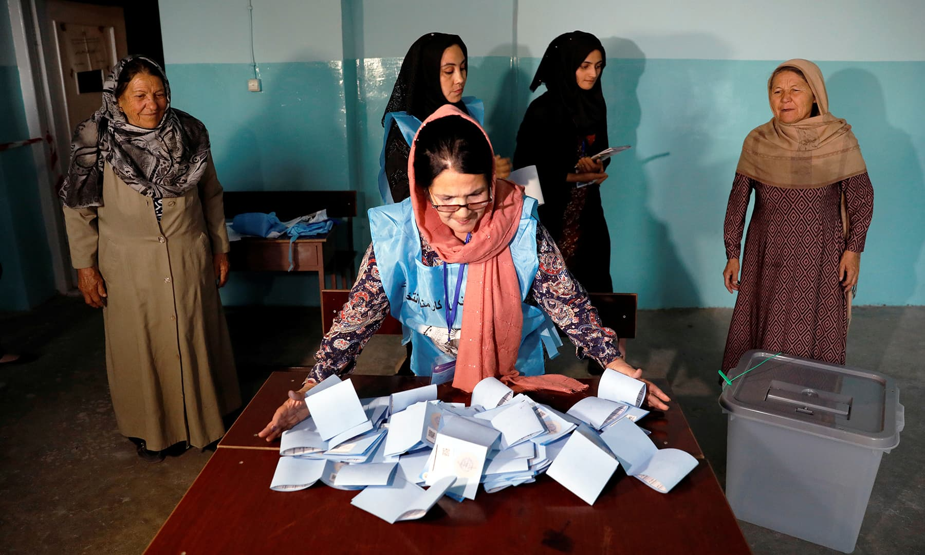 An Afghan election commission worker prepares ballot papers for counting in Kabul. — Reuters