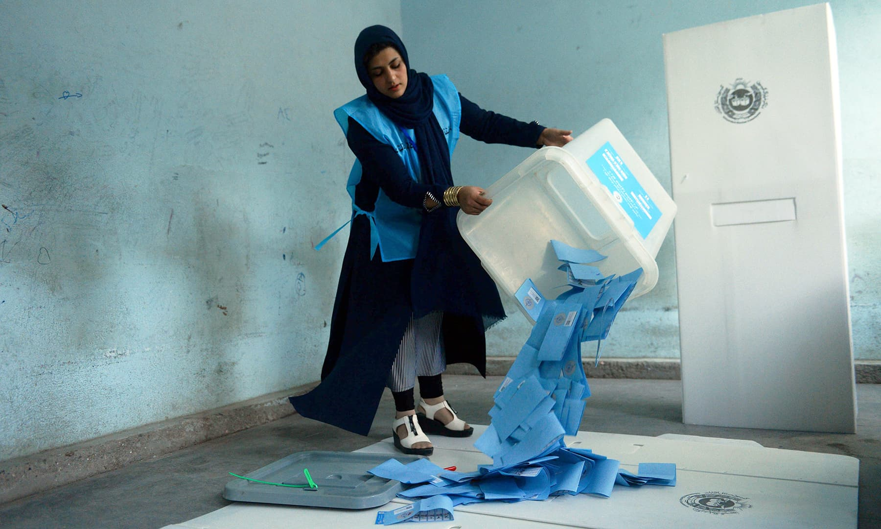 An Afghan Independent Election Commission (IEC) official empties a ballot box to count ballot papers after polling stations closed, in Herat. — AFP