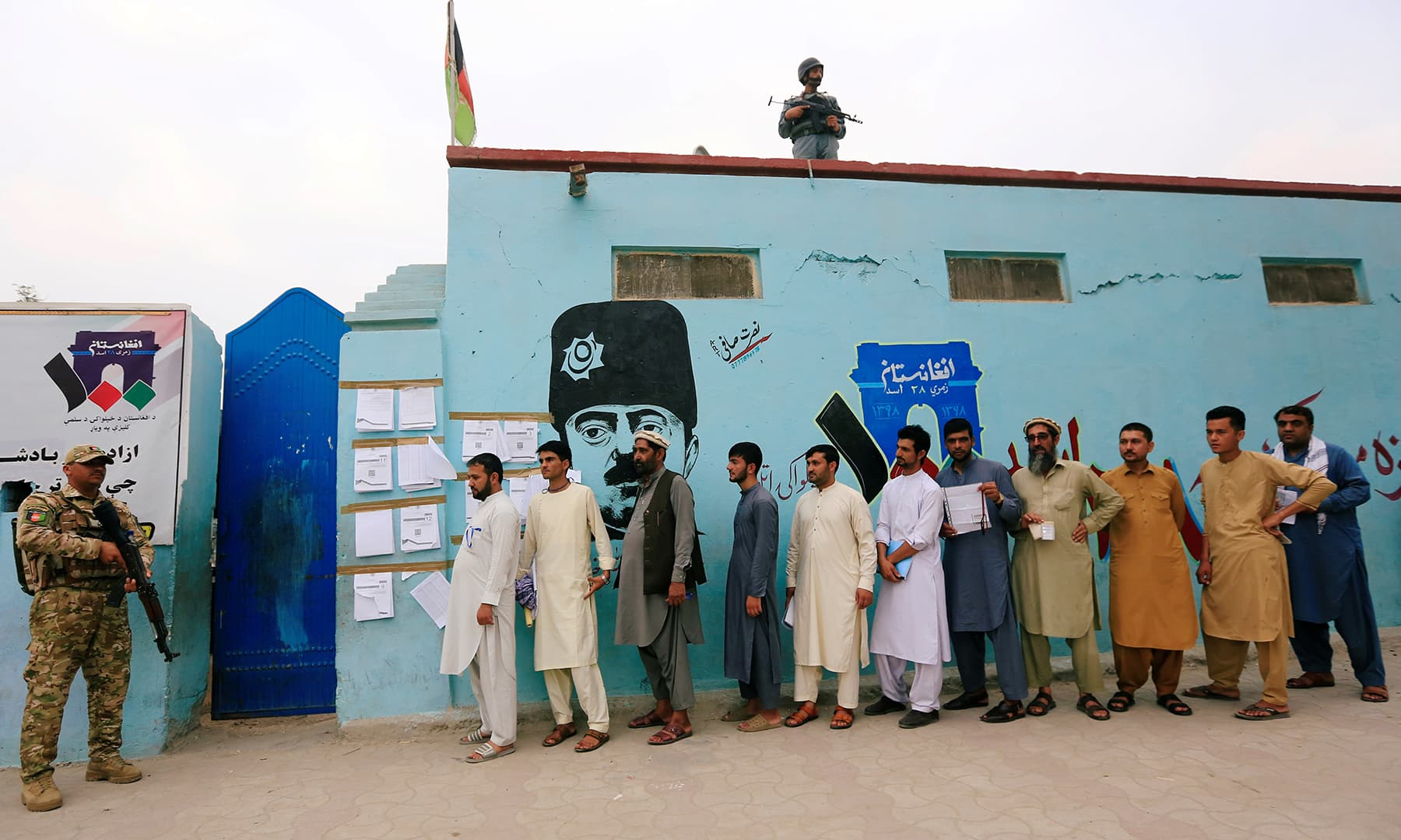 Men arrive to cast their votes outside a polling station in the presidential election in Jalalabad. — Reuters