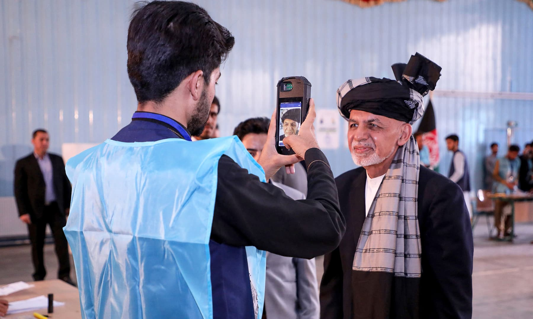 In this handout photograph taken and released by Press Office of President of Afghanistan, an Independent Election Commission (IEC) official scans the face of Afghan President and candidate Ashraf Ghani with a biometric device at a polling station in Kabul. — AFP