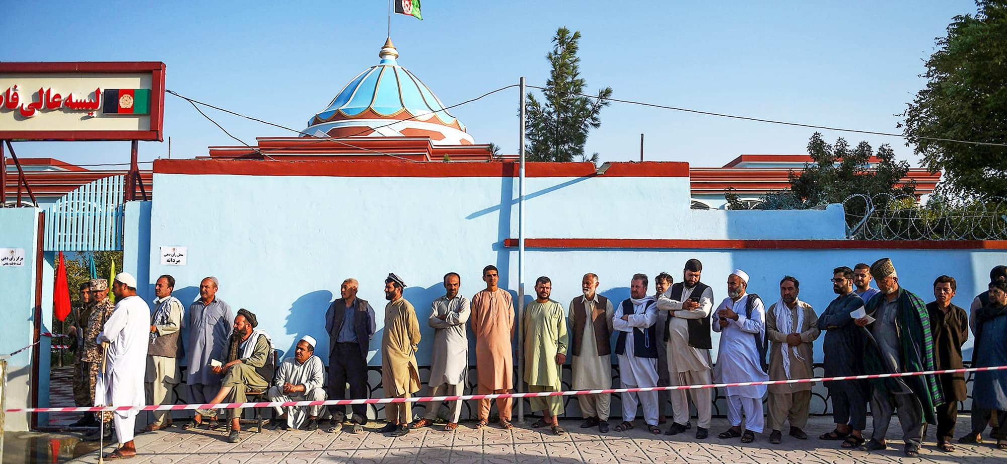 TOPSHOT - Men queue to cast their vote at a polling station in Mazar-i-Sharif on September 28, 2019. - Insurgents worked to disrupt Afghanistan's presidential election on September 28, with a series of blasts reported across the country as voters headed to the polls and troops flooded the streets of the capital. (Photo by FARSHAD USYAN / AFP) — AFP or licensors