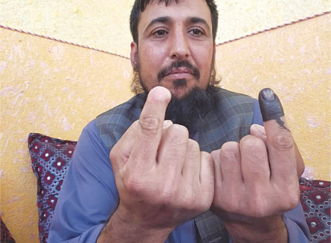 Kabul: Saifullah Safi shows inked finger next to severed finger on Saturday in this picture obtained from social media.—Reuters