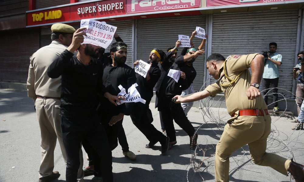 In this September 8 file photo, an Indian police officer charges at members of the Shia community in occupied Kashmir as they attempt to take out a religious procession during restrictions in Srinagar. — AP