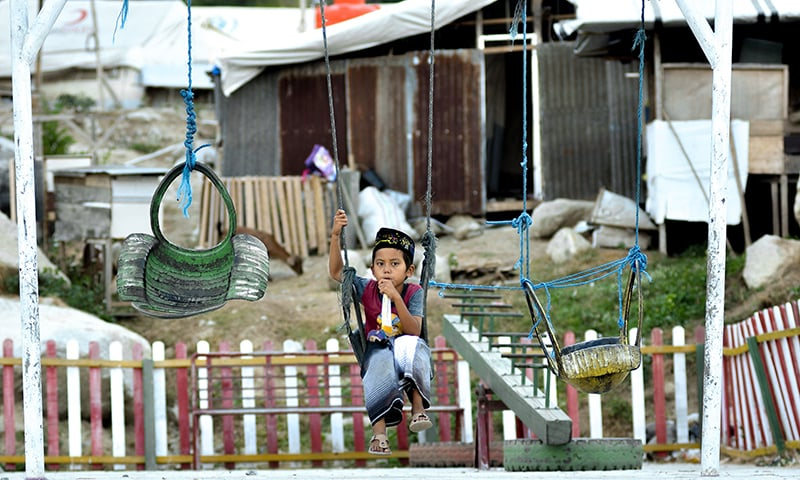 This picture taken on September 25, 2019 shows 9-year-old Rafi Adit Putra sitting on a swing near his living place, a temporary shelter, in Palu, Central Sulawesi, a year after the magnitude 7.5 quake and subsequent deluge razed swathes of the coastal city killing more than 4,300 people and displacing some 170,000 residents. — AFP