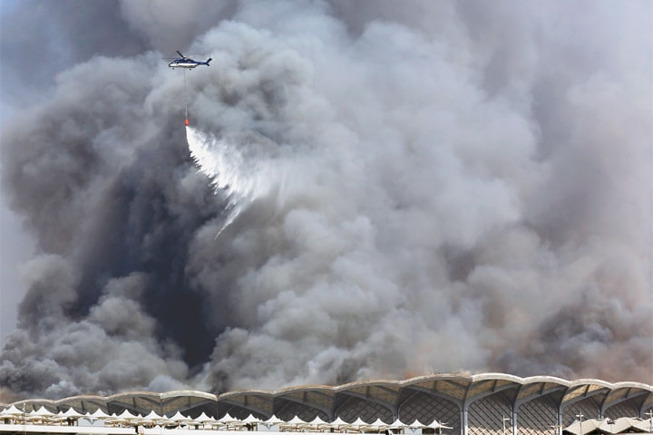 Jeddah: A firefighting helicopter sprays water on the fire.—AP