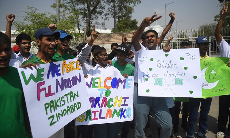 Cricket fans hold placards and cheer as they stand in queue to enter the National Cricket Stadium in Karachi on Monday. — AFP