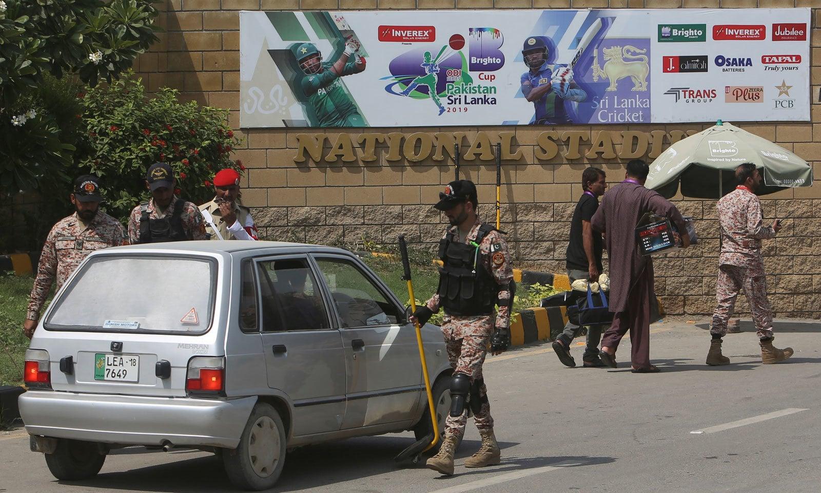 نیشنل اسٹیڈیم کے مرکزی دروازے پر سیکیورٹی آفیشلز گاڑیوں کی چیکنگ کر رہے ہیں— فوٹو: اے ایف پی