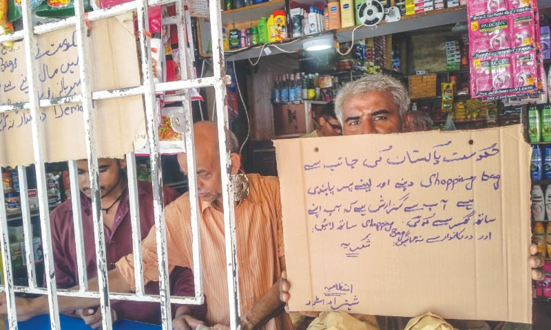 A SHOPKEEPER in North Nazimabad puts up a sign warning customers to bring their own shopping bags while (right) a consumer carries the ubiquitous 'shoppers' on Monday. — Fahim Siddiqi / White Star