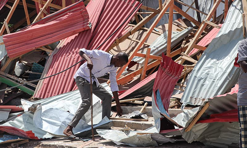A resident tries to scavenge items from his damaged home at the site of a suicide car bomb explosion which targeted a European Union vehicle convoy in Mogadishu, Somalia, on September 30. — AFP