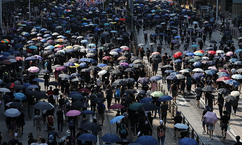Anti-government protesters holding umbrellas march past police headquarters in Hong Kong on Tuesday. — AP