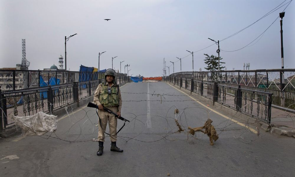 An Indian paramilitary force soldier stands guard near a barbed wire barricade during restrictions in Srinagar Indian occupied Kashmir on September 27. — AP/File