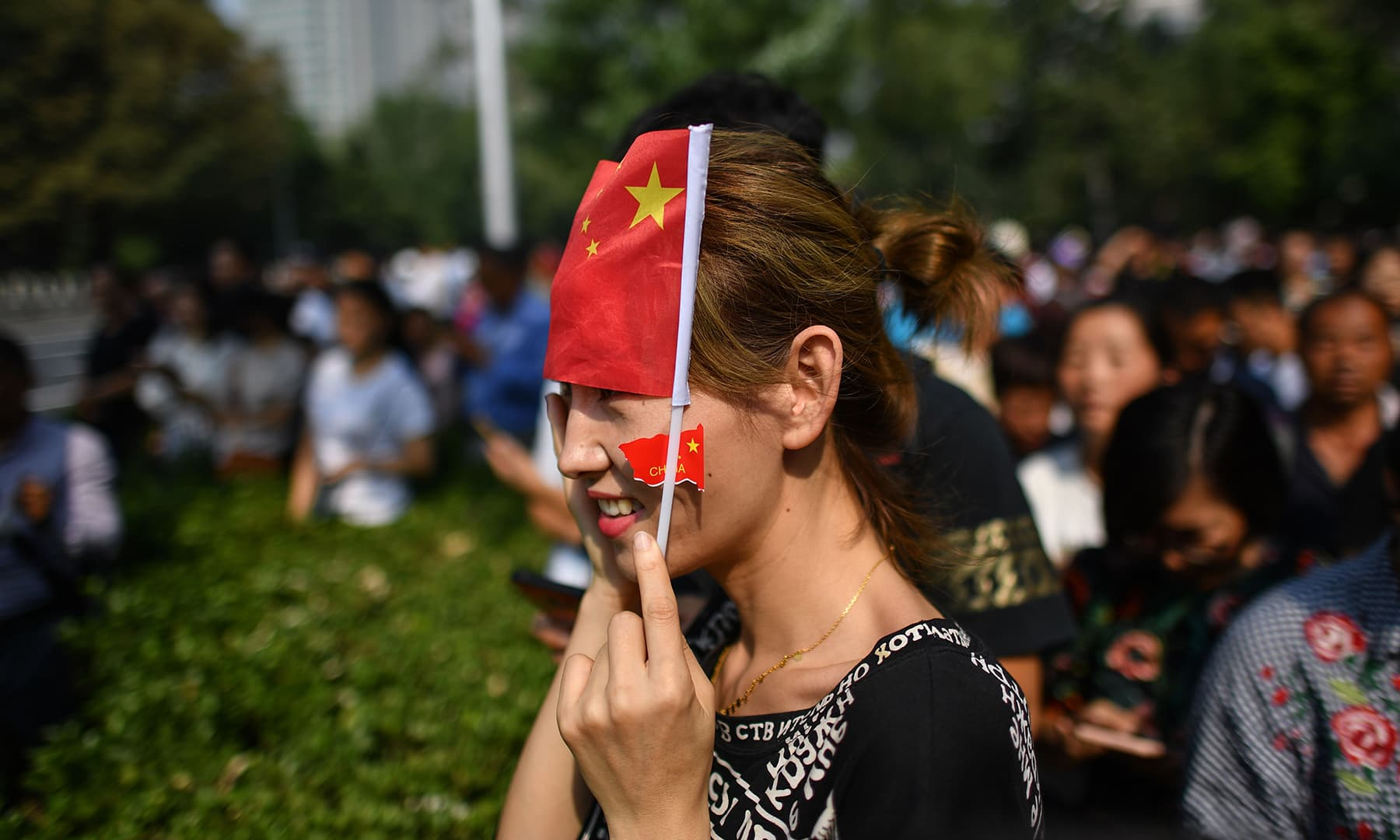 A citizen watches a military parade along the security perimeter established around the official ceremony in Tiananmen Square in Beijing. — AFP