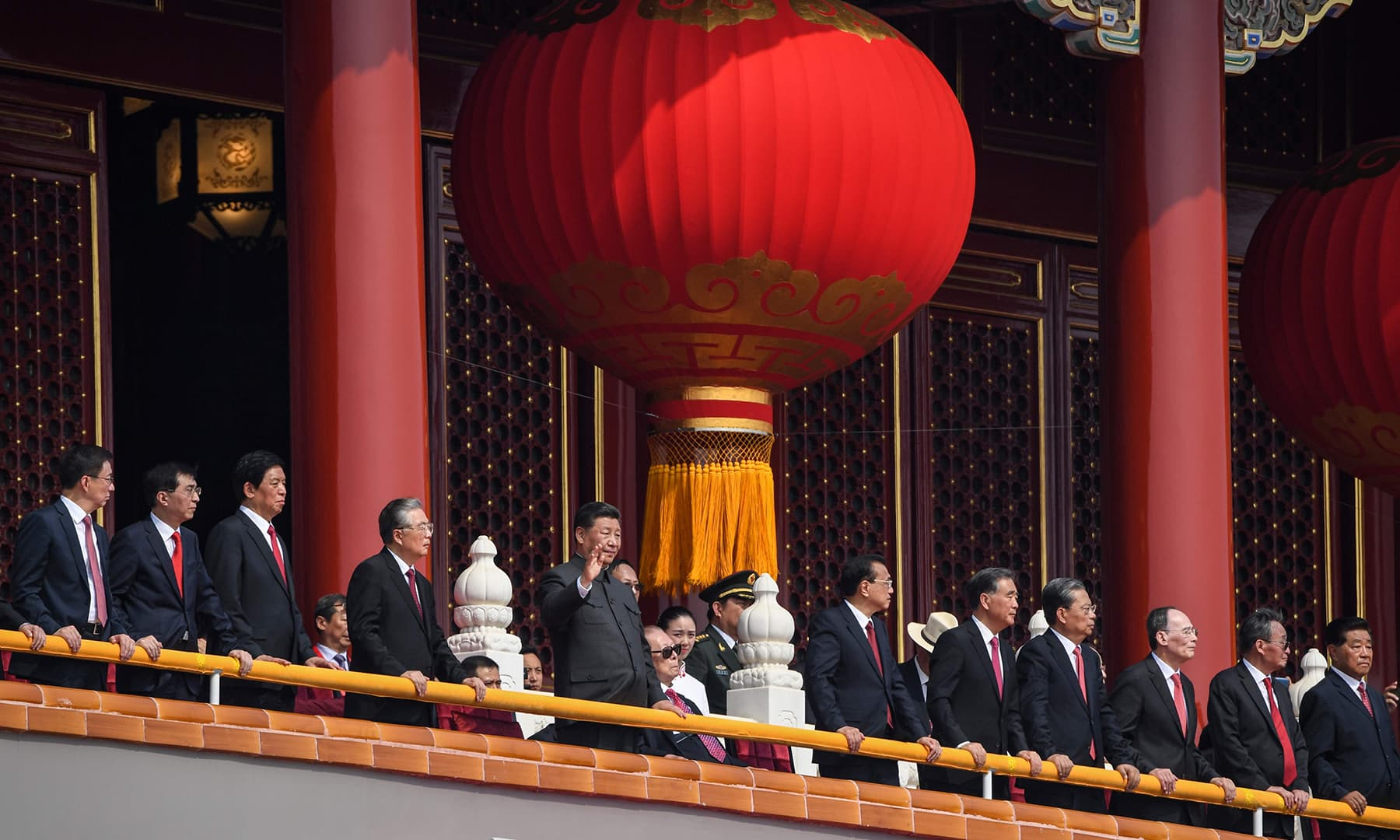 Chinese President Xi Jinping along with other government officials watch a military parade. — AFP