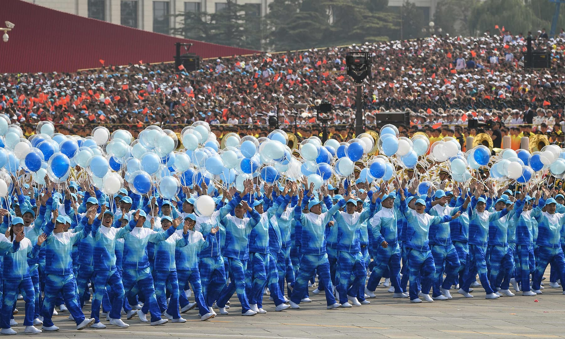 People take part in the National Day parade in Tiananmen Square in Beijing. — AFP