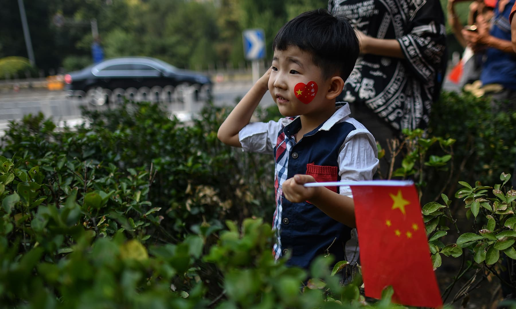 A child watches a military parade along the security perimeter established around the official ceremony in Tiananmen Square in Beijing. — AFP