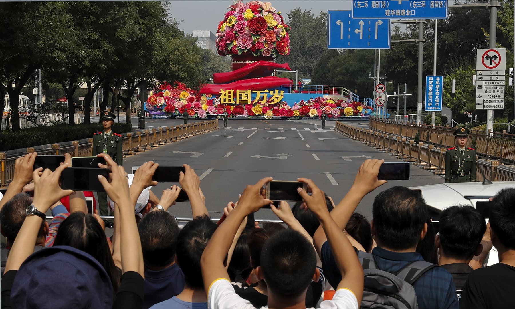 "Residents use smartphone to film a colourful float carrying the words ""Long live motherland"" during the parade. — AP"