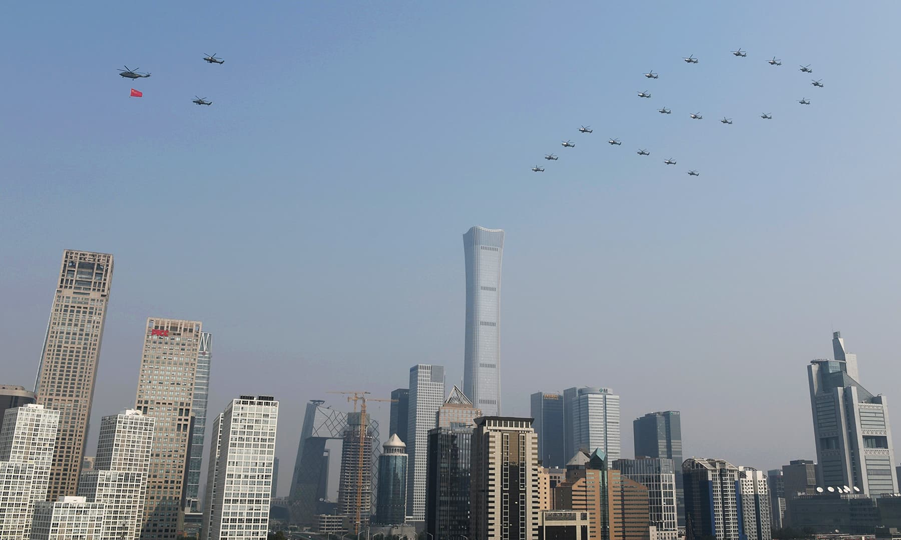 Military helicopters fly over the Central Business District in the formation of the number '70' during the military parade. — Reuters