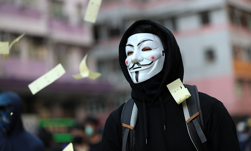 "Ceremonial ""joss paper"" used in memory of those who died for democracy flutters around a protester wearing a Guy Fawkes mask during a demonstration in the Sham Shui Po district in Hong Kong on October 1, as the city observes the National Day holiday to mark the 70th anniversary of communist China's founding. — AFP"