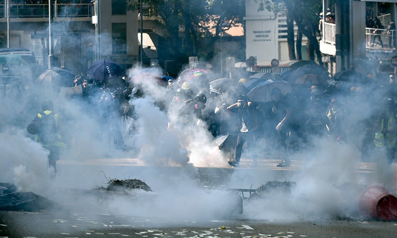 Police fire tear gear to disperse protesters in Tsuen Wan district in Hong Kong on Tuesday. — AFP