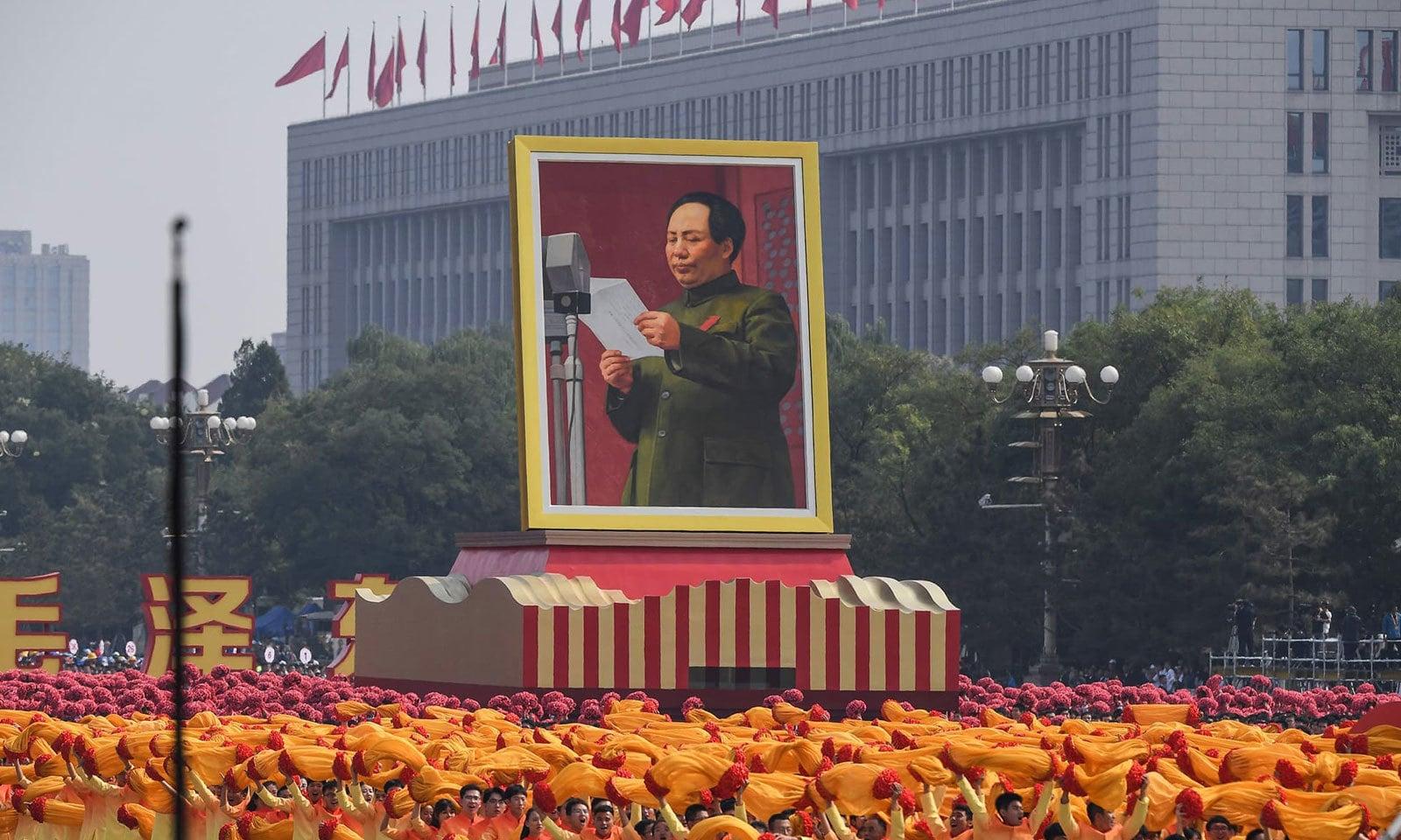 چین کے یوم آزادی کی تقریب کے دوران تیانامن اسکوائر سے کمیونسٹ پارٹی کے سابق سربراہ ماؤ زے تنگ کی تصویر لے جائی جارہی ہے فوٹو: اے ایف پی