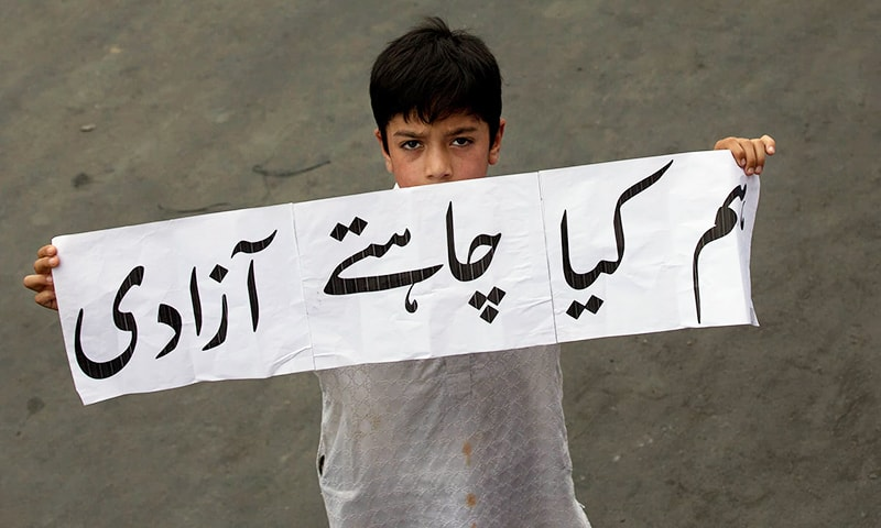 In this Associated Press photograph taken by Dar Yasin on August 9, a Kashmiri boy at a protest march in Srinagar holds a banner that reads 'Hum kya chahte, azadi' (What do we want ─ Freedom). — AP