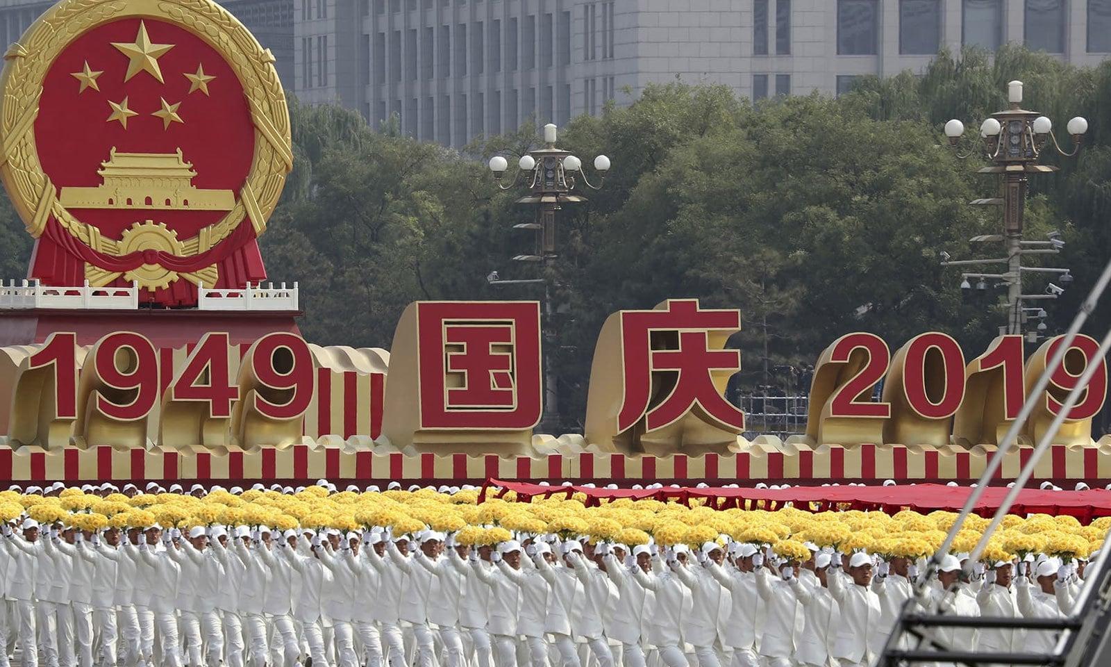 چین کے 70ویں یومِ آزادی کی تقریب کے دوران شرکا مارچ کر رہے ہیں — فوٹو: اے پی
