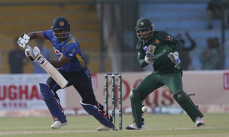 Sri Lankan batsman Danushka Gunathilaka hits boundary as wicketkeeper and captain Sarfaraz Ahmed looks on during a match in Karachi on October 2. — AP