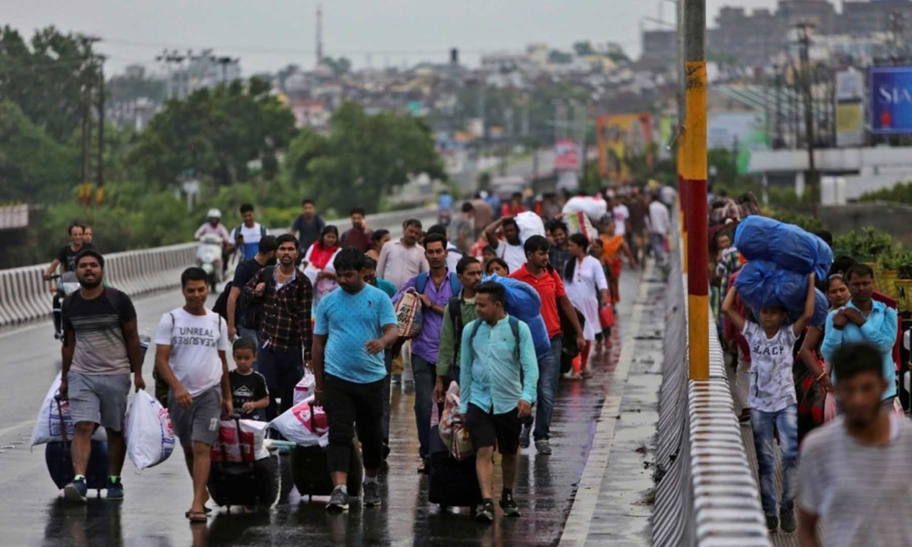 Stranded Indian tourists walk to a railway station during restrictions in IoK on Aug 5. — AP