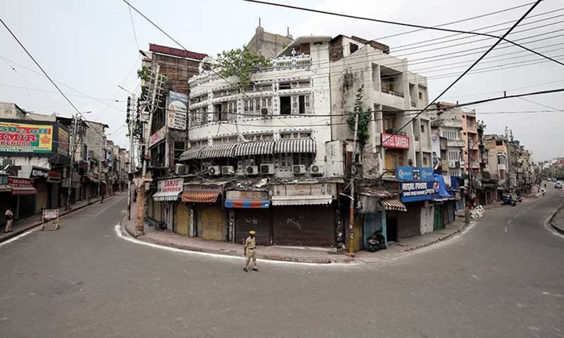 Indian policemen stand guard in a deserted street during restrictions in occupied Kashmir on Aug 6. — Reuters