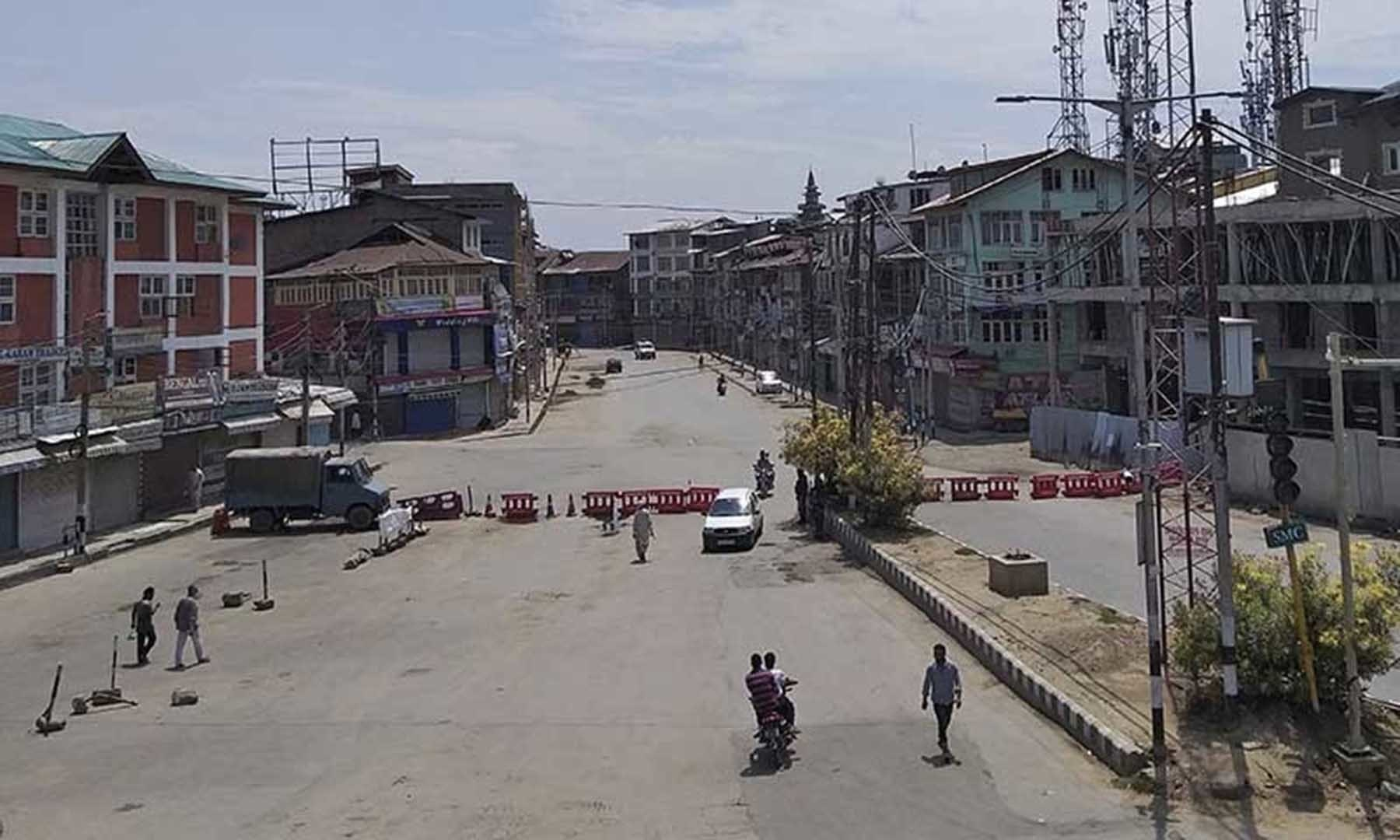 Pedestrians move on a deserted street in Srinagar in occupied Kashmir on Aug 9. — AP