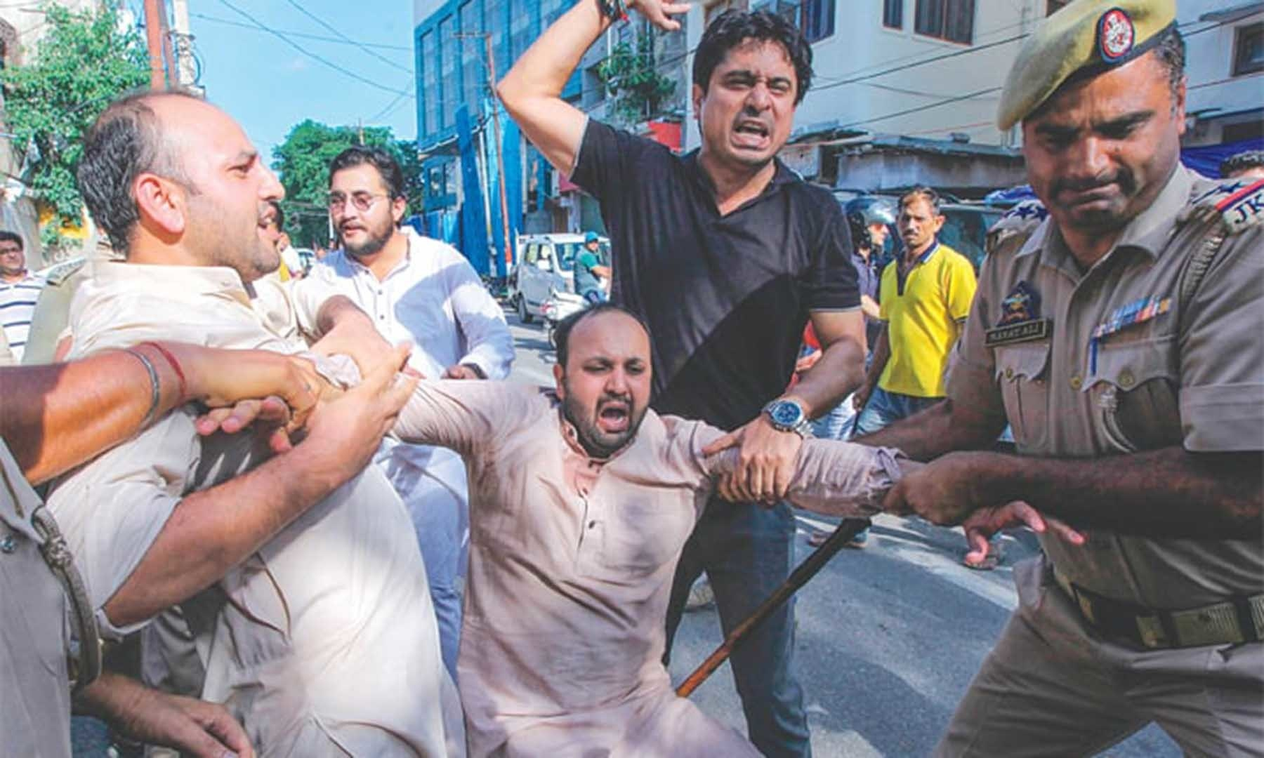 Police taking an activist of Jammu and Kashmir Youth Congress into custody during a protest against the Indian government on Aug 10.—AFP