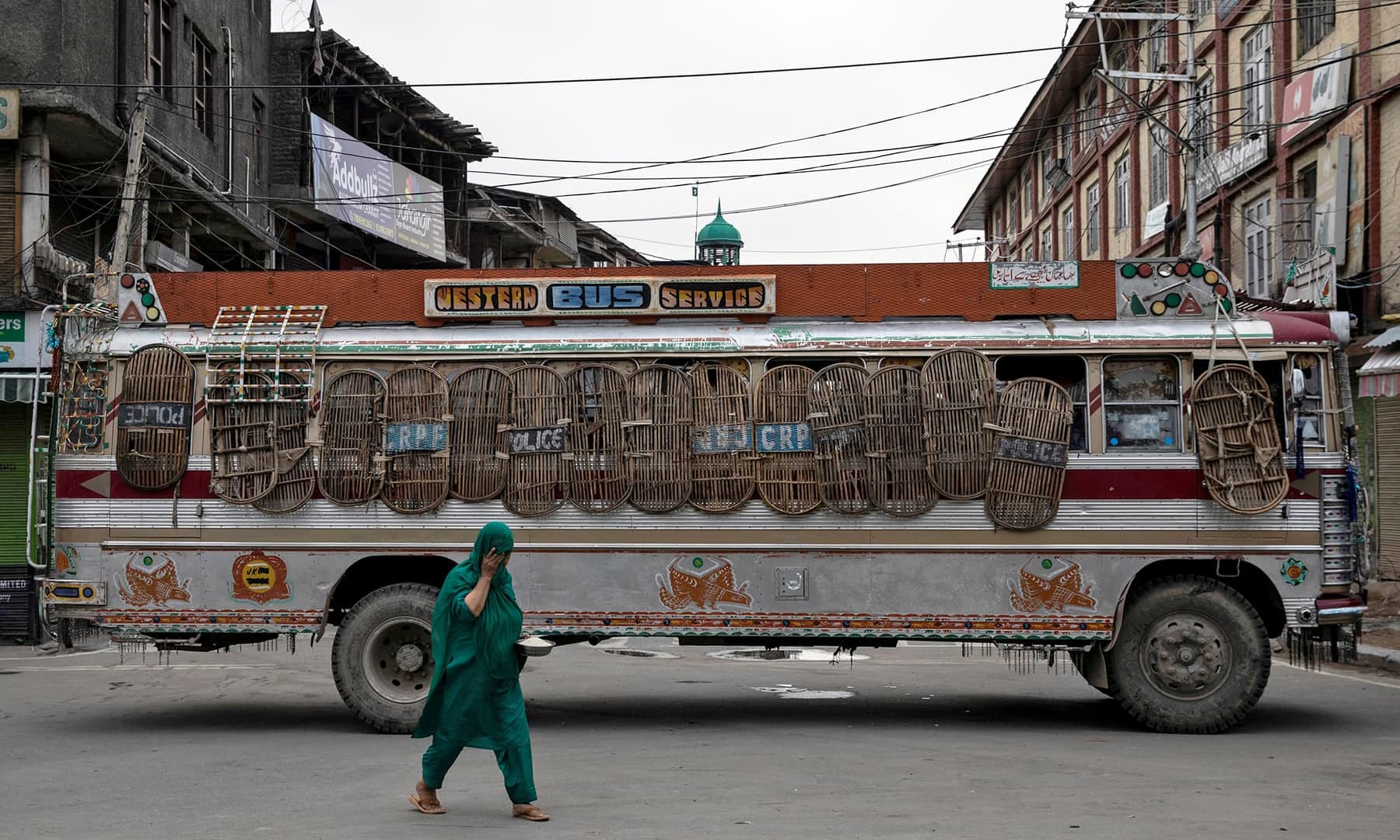 A Kashmiri woman walks past a bus used as a road block by Indian security personnel during restrictions, in Srinagar, Aug 11. — Reuters