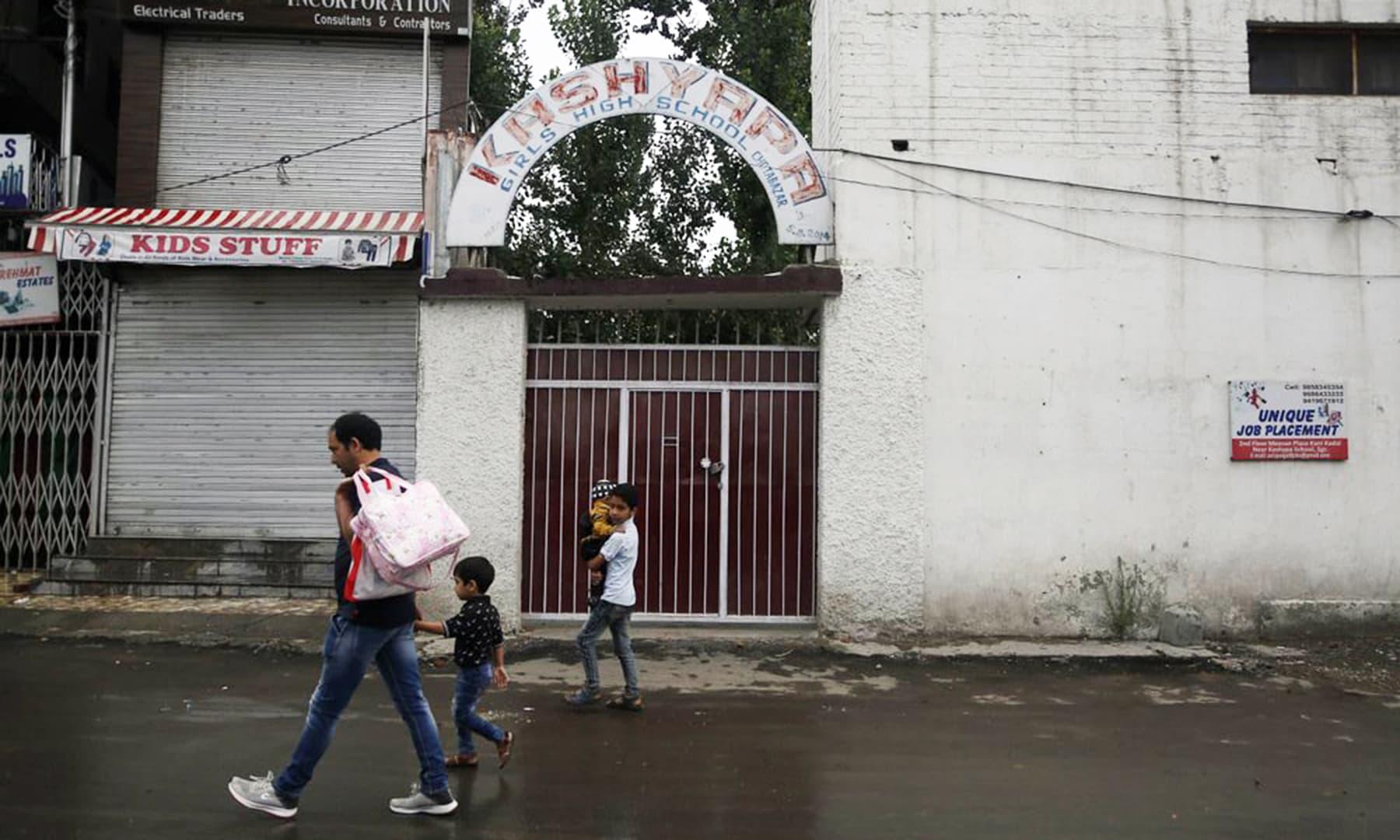 Kashmiris walk outside a closed school in Srinagar on Monday. — AP