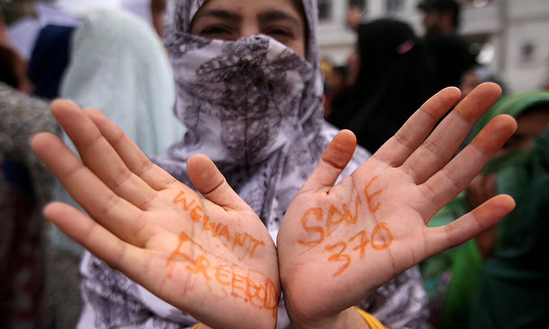 A Kashmiri woman shows her hands with messages at a protest after Friday prayers during restrictions in Srinagar, August 16. — Reuters