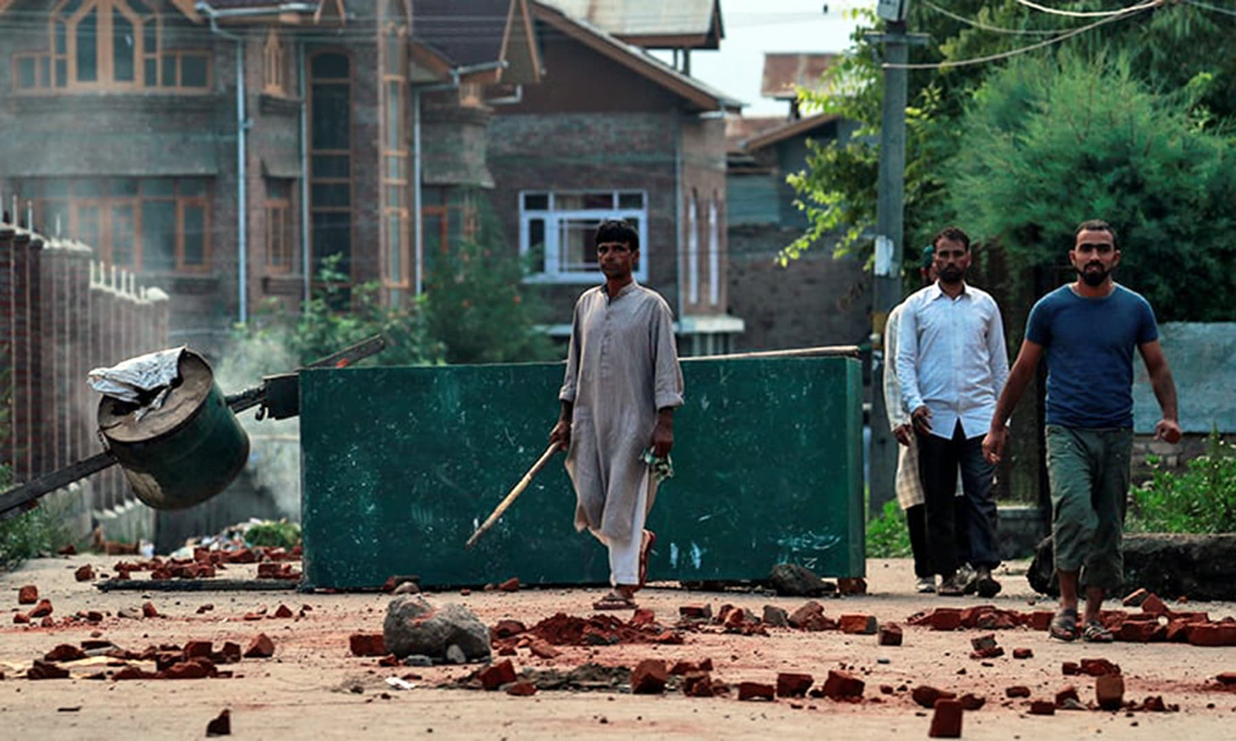 Kashmiris walk past a blockade put up by residents to prevent security personnel from sealing off a mosque ground ahead of Eiul Azha prayers during restrictions in Srinagar, August 12. — Reuters