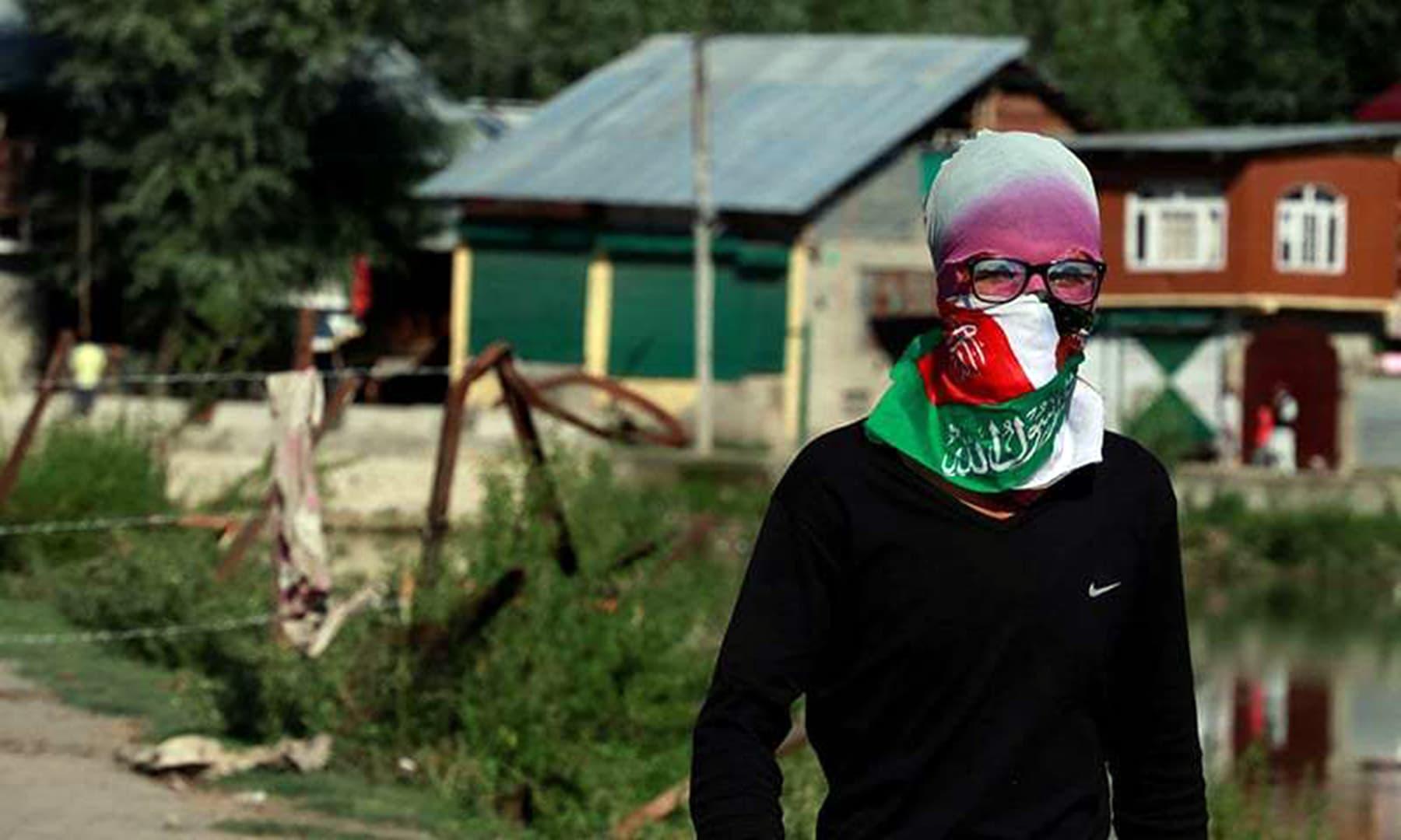 A Kashmiri masked protester stands near a barricade to block the entrance of a neighbourhood in Srinagar, August 19. — Reuters