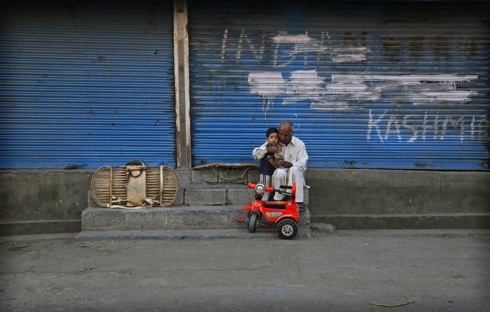 A man feeds a child outside a closed shop during the curfew in Srinagar. — AP