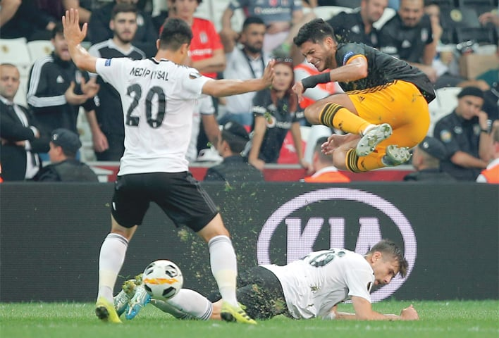 ISTANBUL: Besiktas' Necip Uysal (L) and Dorukhan Tokoz stop Wolverhampton Wanderers' Raul Jimenez during their Group 'K' match at Besiktas Park.—AP
