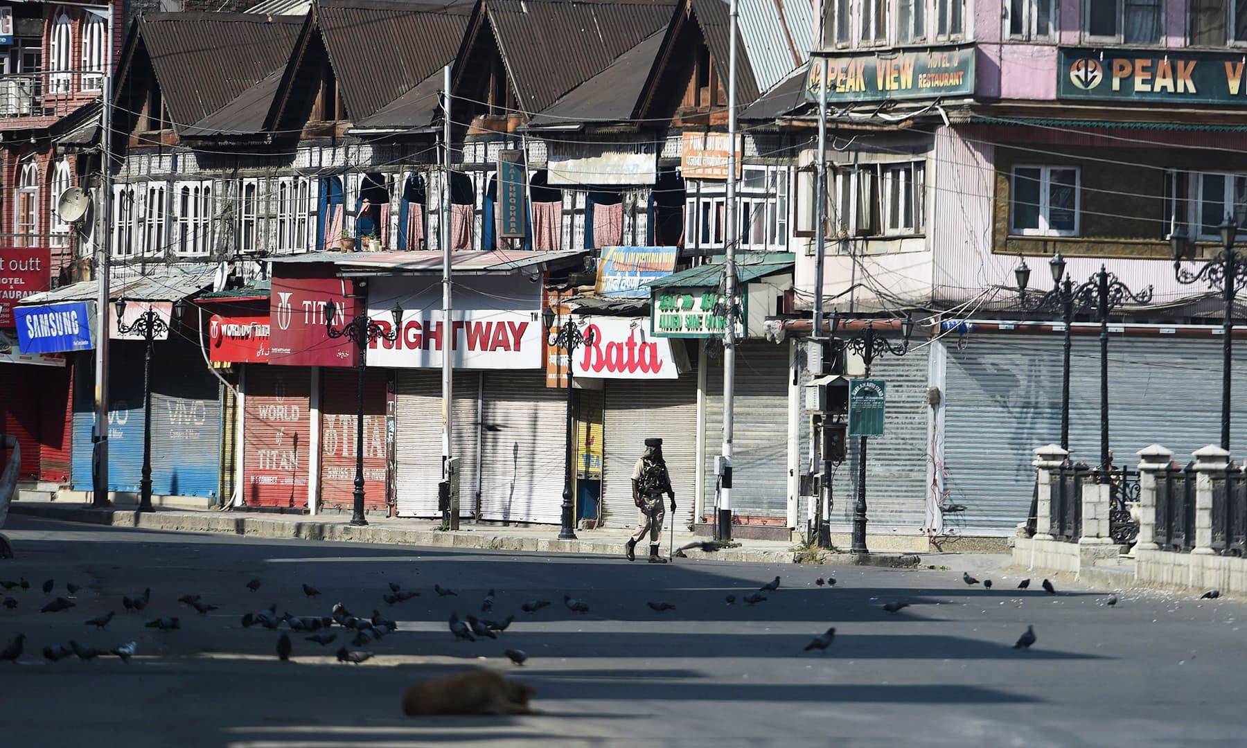 In this file photo taken on September 8, an Indian paramilitary trooper patrols along an empty street during a strict curfew in Srinagar. — AFP