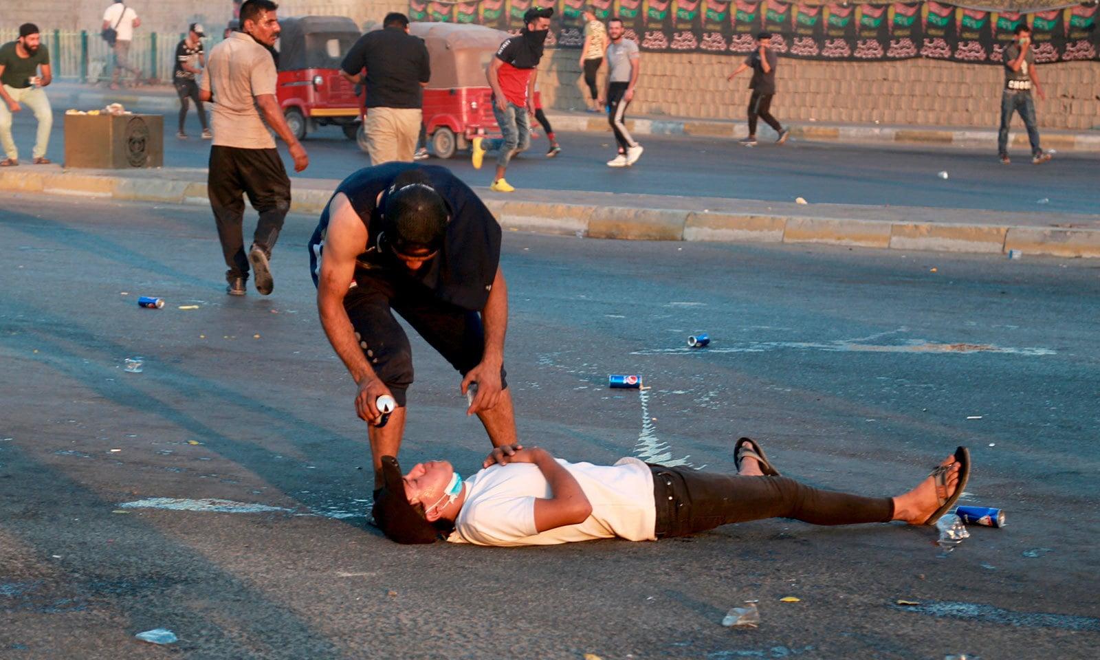 بغداد میں مظاہرے کے دوران زخمی ہونے والا ایک شخص زمین پر لیٹا ہوا ہے — فوٹو: اے پی