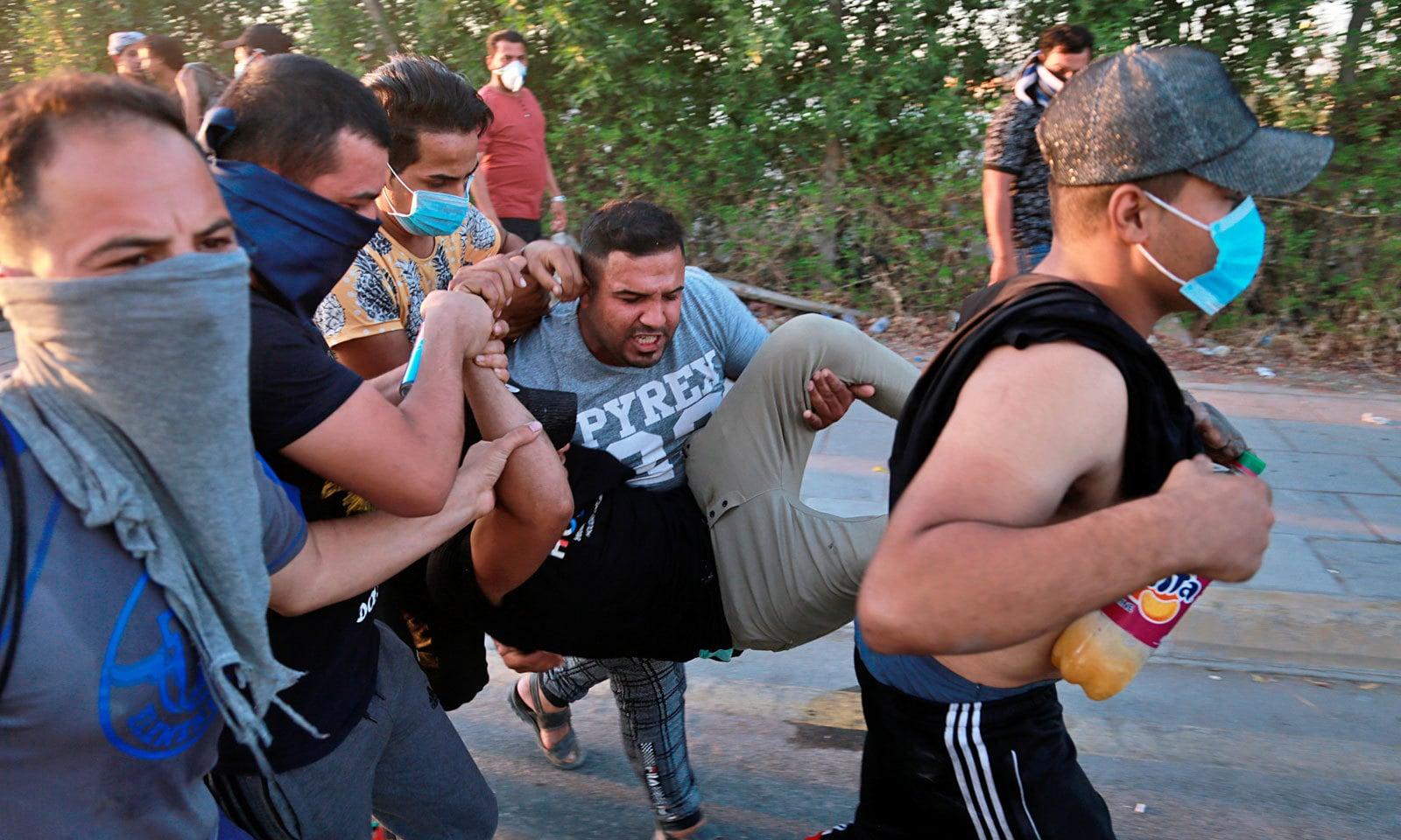 مظاہرے کے دوران زخمی ہونے والے ایک شخص کو ہسپتال منتقل کیا جارہا ہے — فوٹو: اے پی