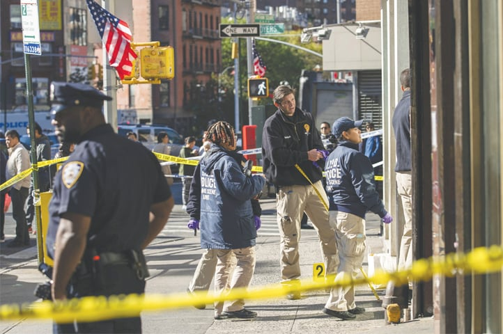 New York Police Department officers investigate the scene of an attack in Manhattan's Chinatown neighborhood on Saturday.—AP
