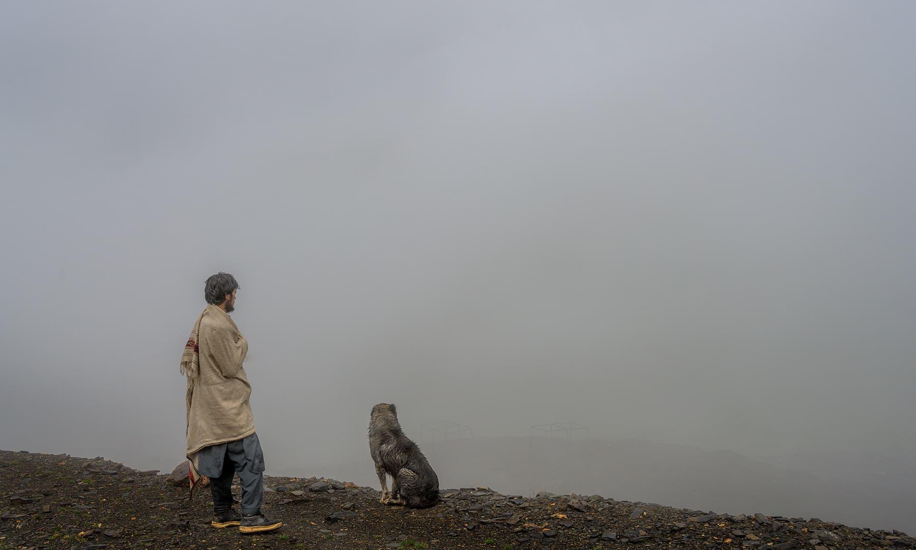 بابوسر پاس کے مقام پر ایک کوہستانی نوجوان اپنے پالتو کتے کے ساتھ