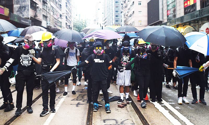 Hong Kong lashed by fresh violence as thousands defy mask ban