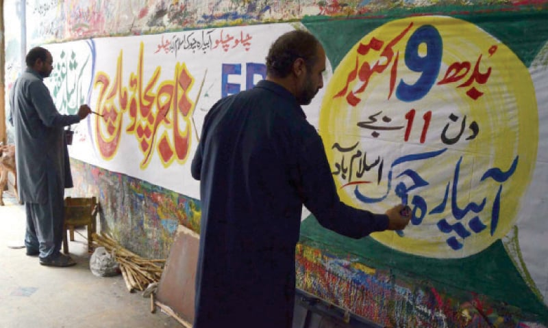 Painters prepare a banner in connection with the traders' protest in Islamabad. —INP