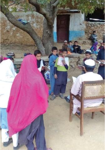 A teacher takes a class in the open in Hanjoo area of Battagram. —Dawn