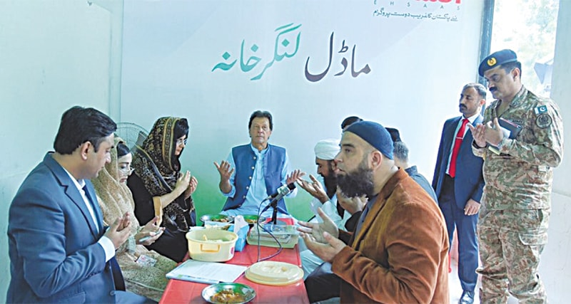 ISLAMABAD: Prime Minister Imran Khan prays before eating food after the inauguration of 'Model Free Kitchen' under the Ehsaas programme on Monday.—PID