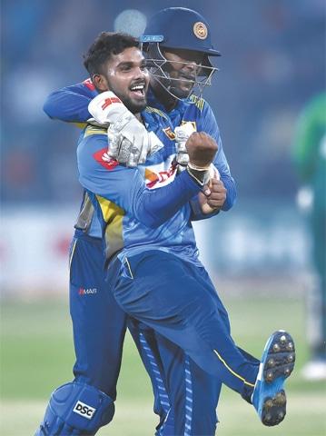 LAHORE: Sri Lanka's spinner Wanindu Hasaranga (left) celebrates with wicketkeeper Minod Bhanuka after the dismissal of Pakistan's captain Sarfraz Ahmed during the second Twenty20 match at the Gaddafi Cricket Stadium on Monday. In an excellent performance, Sri Lanka beat Pakistan by 35 runs. Bhanuka Rajapaksa scored an aggressive maiden half-century as Sri Lanka made 182-6 while Hasaranga took three wickets. Rajapaksa was declared man of the match.—AFP